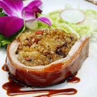 Glutinous rice cooked with five grains is stuffed into a whole suckling pig then roasted. The final